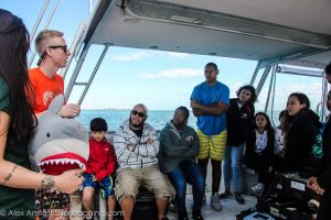 Trip leader and SRC Master's student Jake tells students about the workup process for a shark and uses Sharky, the stuffed shark, to demonstrate the procedures