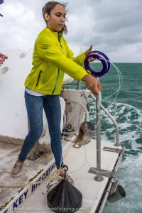 A MAST Academy student tosses the barracuda bait into the water.